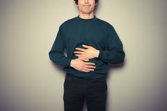 Young man rubbing his stomach. A young man is rubbing his stomach Royalty Free Stock Image
