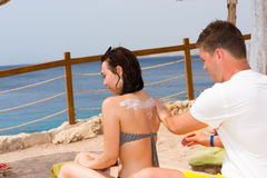 Young man rubbing sunscreen lotion onto back of woman. Young men rubbing sunscreen lotion onto back of women while relaxing together in vacation royalty free stock photography