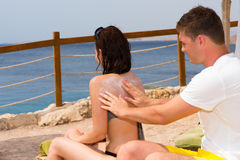 Young man rubbing sunscreen lotion onto back of woman while relaxing together in vacation and seating on sunbeds. Young men rubbing sunscreen lotion onto back of stock image