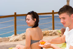 Young man rubbing sunscreen lotion onto back of young woman. Young men rubbing sunscreen lotion onto back of young women while relaxing together in vacation stock image