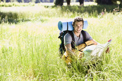 Young man, with rucksack, sitting in woodland clearing, consulting map on hiking trip, smiling, portrait Royalty Free Stock Photo