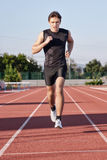 A young man run a hundred meters. Man run a hundred meters on the treadmill Stock Photography
