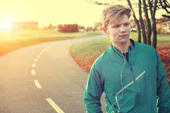 Young man runner with headphones in autumn park Royalty Free Stock Photography