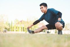 Young man runner stretching legs before run. Young fitness man runner stretching legs before run Royalty Free Stock Images