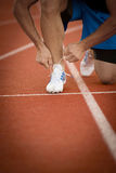 Young Man Runner tying his shoes on a running track. Shoelaces, Urban jogger.  Royalty Free Stock Photo