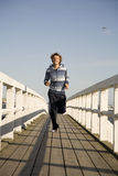 Young man running. On the wooden bridge Royalty Free Stock Photos