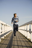 Young man running. On the wooden bridge Stock Image