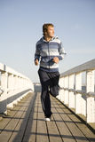 Young man running. On the wooden bridge Stock Photography