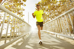 Young man running across a bridge Royalty Free Stock Image