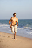Young Man Running Along Summer Beach. In The Sun Royalty Free Stock Photo