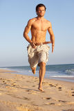 Young Man Running Along Summer Beach. In The Sun Stock Photo
