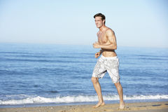 Young Man Running Along Summer Beach Stock Photos
