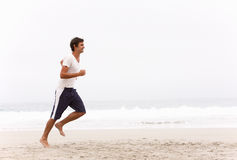 Young Man Running Along Winter Beach. Smiling Royalty Free Stock Photos