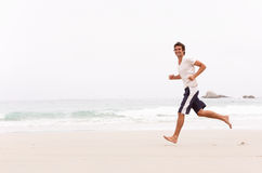 Young Man Running Along Winter Beach. Smiling Stock Images