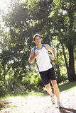 Young Man Running Along Woodland Path Stock Photo