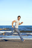 Young man running barefoot on beach Royalty Free Stock Images