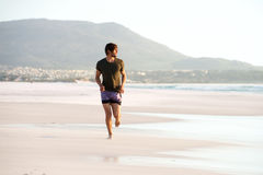 Young man running barefoot on beach Stock Photos