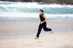 Young Man Running on Beach Stock Image