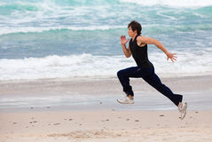 Young Man Running on Beach Stock Photography