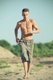 Young man running on beach Royalty Free Stock Image