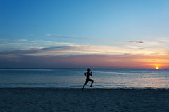 Young man running on the beach Stock Image