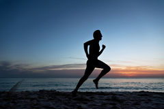 Young man running on the beach Stock Photo