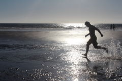 Young man is running on the beach along the seacoast. Royalty Free Stock Photography