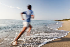 Young man running on a beach. stock images