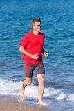 Young man running on the beach in Costa Brava, Spain Royalty Free Stock Image