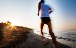 Young man running on a beach at sunrise. Motion blur effect. Stock Photo