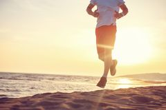 Man running on the beach at sunset. Young Man running on the beach at sunset Stock Photos