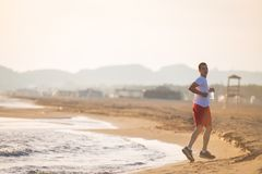 Man running on the beach at sunset. Young Man running on the beach at sunset Stock Photo