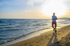 Man running on the beach at sunset. Young Man running on the beach at sunset Stock Images