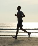 Young man running on the beach by water Royalty Free Stock Photography