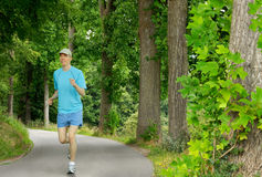 Young man running in a beautiful park Stock Photo