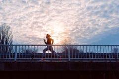 A young man running on the bridge stock photos