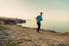 Young man running on coastline Stock Images