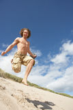Young Man Running Down Sand Dune. On Beach Royalty Free Stock Photos