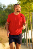 Young man running with earphones outside Stock Photography