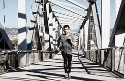 Young man running with earpieces Royalty Free Stock Photos