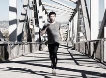 Young man running with earpieces Stock Photography