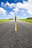 Young man running on the empty road Stock Photo
