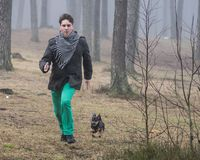 Young man running fast in forest. Young man running fast taking compete in forest with little dog Royalty Free Stock Photography