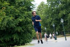 Young man running on footpath Stock Images