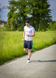 Young man running and jogging on road in country Stock Image