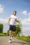 Young man running and jogging on road in country Royalty Free Stock Photos