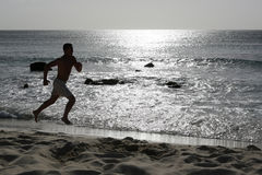 Young man running or jogging training on the beach Stock Image
