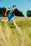 Young man running through meadows Stock Photos