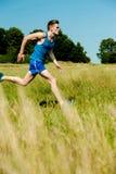 Young man running through meadows Stock Photos