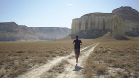 A young man is running in the middle of a mountainous area stock footage